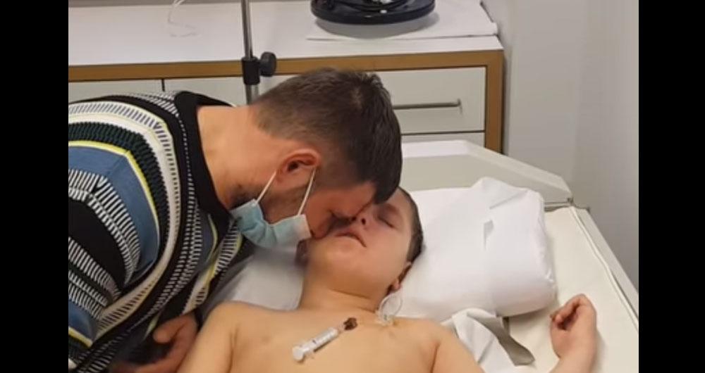 Отец плачет у постели больного сына Ромы из Бучи. У мальчика рак головного мозга