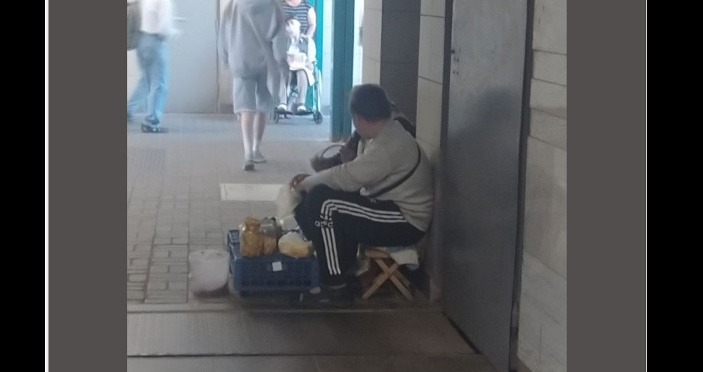 «На метро АкадемМістечко в переході сидять хлопчик підліток з бабусею. Хлопчик на костилях»